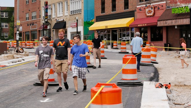 Pedestrians walk between traffic barrels on a strip of pavement along State Street Wednesday, July 19, 2017, in West Lafayette. State Street is scheduled to open once again August 13, one day before freshmen are due to arrive on campus.