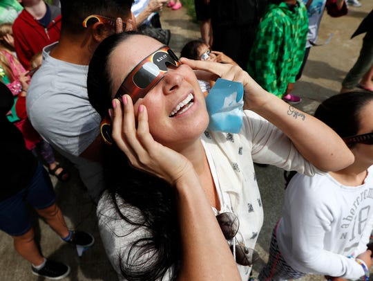 Heather Sandoval, of Des Moines, Iowa, holds her glasses
