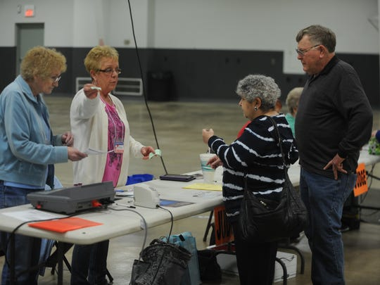 Amie Sue Felty and Trinda Thomas instruct Cathy and Bill Cox at the Kuhlman Center vote center.