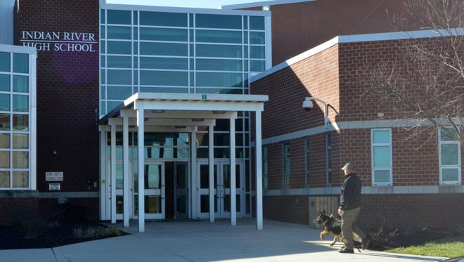 An officer and K-9 police dog sweep the perimeter of Indian River High school after a bomb threat was called in Jan. 11.