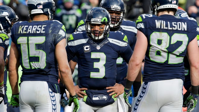 Seattle Seahawks quarterback Russell Wilson (3) speaks with his team during the third quarter against the Carolina Panthers in a NFC Divisional round playoff game at Bank of America Stadium.