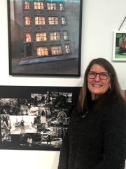 """Diane Phares at a reception with one of her artworks entitled """"Charlie's Sweatshop."""""""