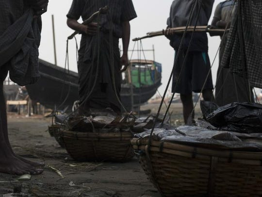 Men with baskets of fish in Theychung village.