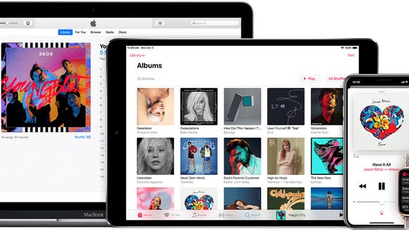 Apple Music interface shown on a Macbook, iPad, iPhone, Apple Watch, and an Apple TV.