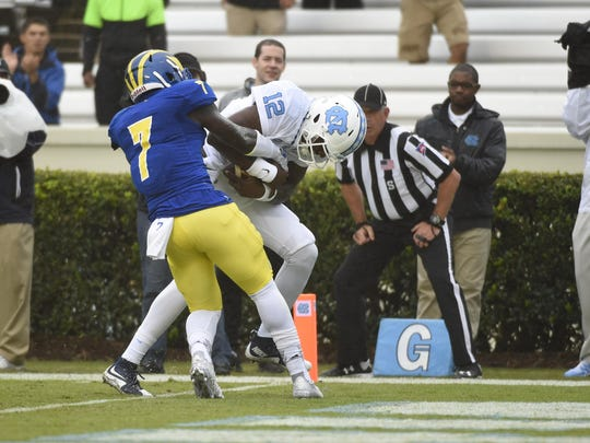 North Carolina Tar Heels quarterback Marquise Williams (12) scores a touchdown as Delaware Blue Hens defensive back Ray Jones (7) defends in the first quarter at Kenan Memorial Stadium.