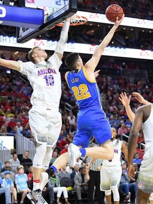 UCLA forward TJ Leaf (22) shoots against the defense of Arizona forward Lauri Markkanen (10) during the Pac-12 tournament semifinals.