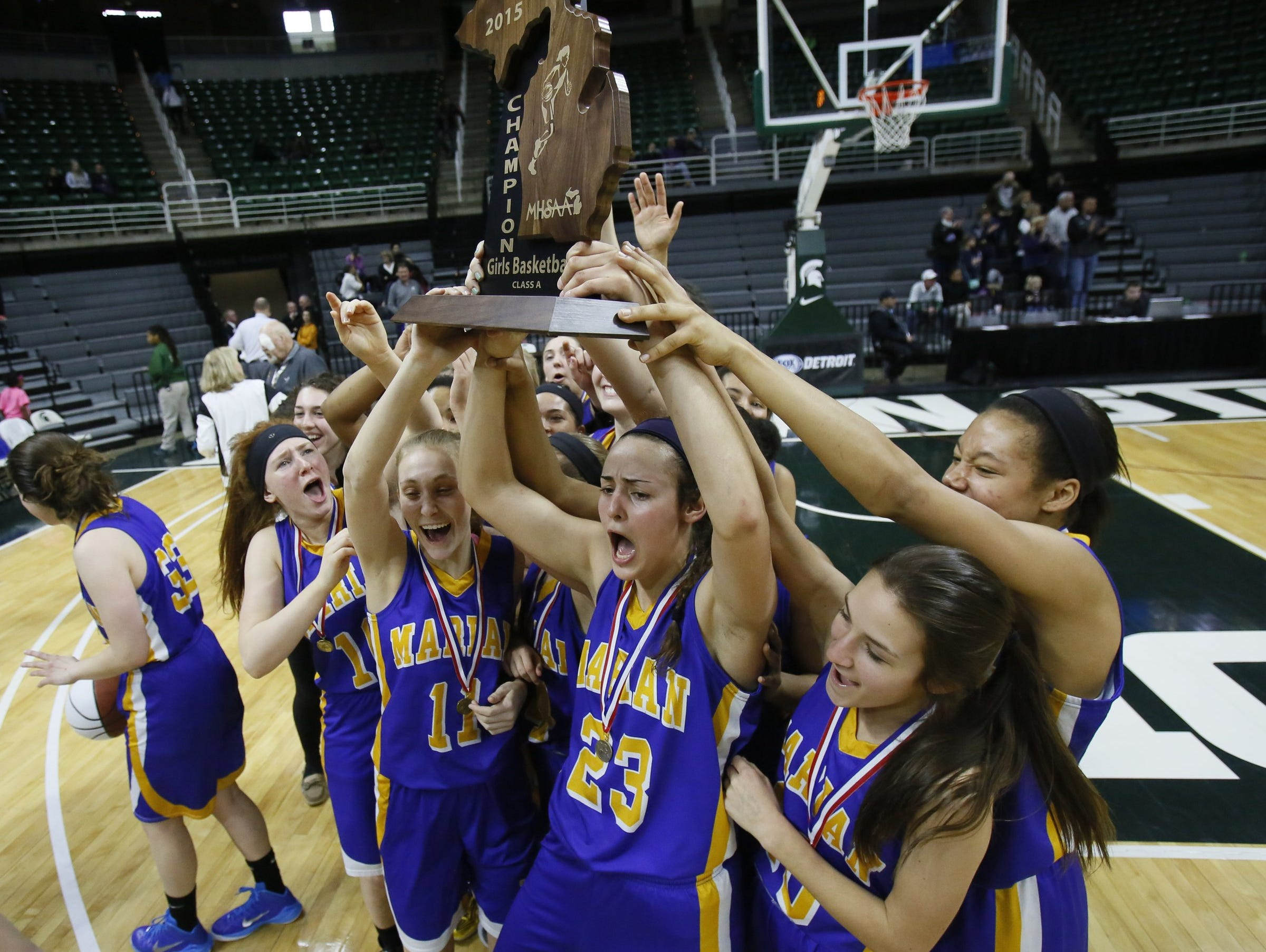 Bloomfield Hills Marian players celebrate for the TV camera's with the championship trophy after their 51-37 win over Dewitt in Class A girls basketball final on March 21, 2015, in East Lansing.