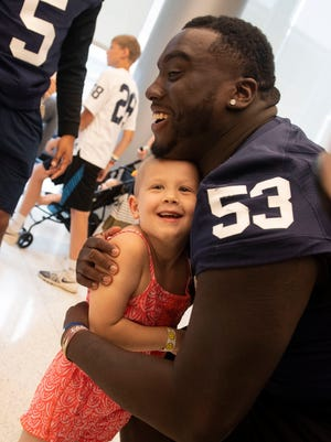 Devin Pulasiki, 5, hugs Penn State's Fred Hansard after taking a group photo at Wednesday's event at the Penn State Children's Hospital at Hershey's Medical Center.