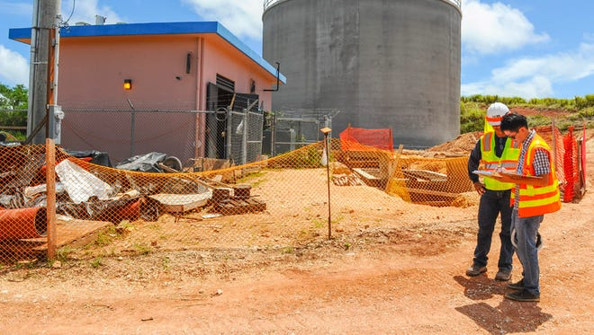 Garrett Yeoh, right, Guam Waterworks Authority senior engineer, logs in at the agency's Chaot water tank #1 construction site located in the hills of Ordot on May 28, 2015. The concrete tank in the background can hold 500,000 gallons of water, said Yeoh.