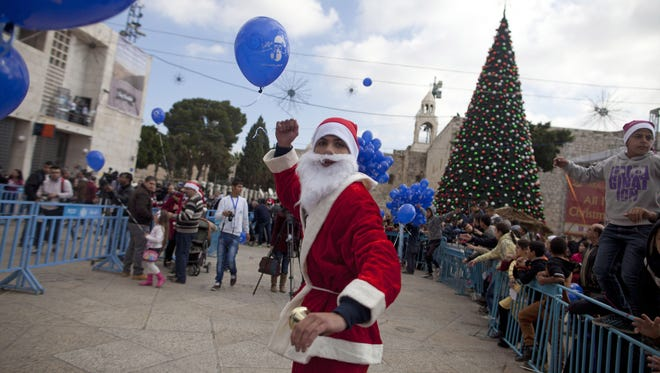 A Palestinian man dressed in a Santa Claus costume gives out balloons outside the Church of the Nativity on Dec. 24, 2014 in Bethlehem, West Bank. Every Christmas pilgrims travel to the church where a gold star embedded in the floor marks the spot where Jesus was believed to have been born.