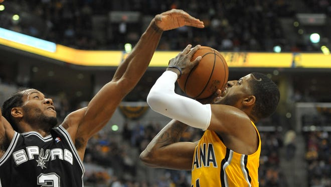 Indiana's Paul George tries to shoot over San Antonio's Kawhi Leonard in the third quarter as the San Antonio Spurs beat the Indiana Pacers 103-77 at Bankers Life Fieldhouse, March 31, 2014.