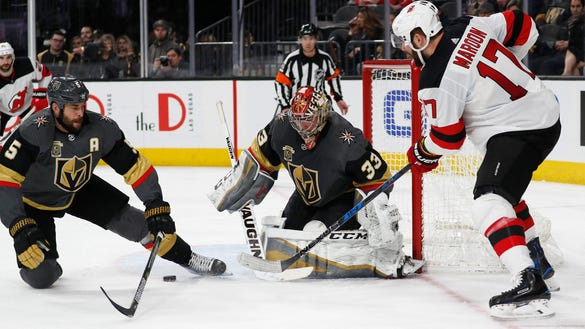 New Jersey Devils left wing Patrick Maroon (17) passes the puck between Vegas Golden Knights goaltender Maxime Lagace and defenseman Deryk Engelland during the third period of an NHL hockey game Wednesday, March 14, 2018, in Las Vegas. (AP Photo/John Locher)