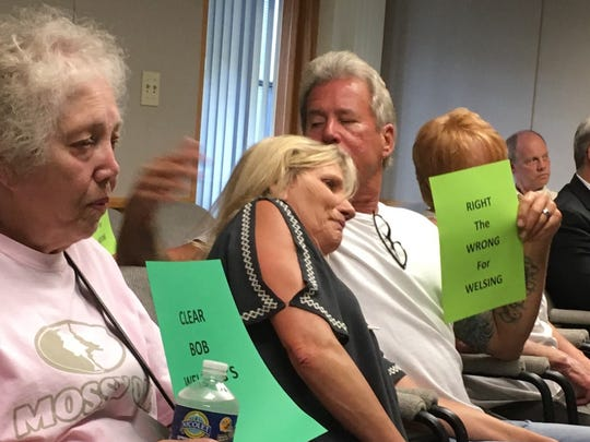 Family members of the late Robert Welsing Jr. hold signs urging Brown County lawmakers to overturn Welsing's firing and grant his reinstatement as a supervisor in the county Highway Department.
