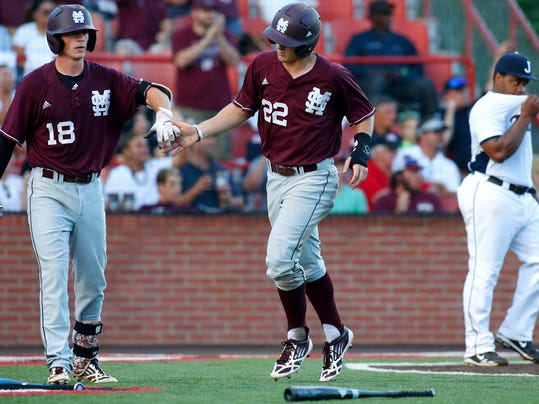 Mississippi State's Jake Vickerson (22) celebrates with Seth Heck (18) after scoring on a ball hit by Derrick Armstrong in the sixth inning during an NCAA college baseball tournament regional game against Jacksonville State  in Lafayette, La., Saturday, May 31, 2014. Mississippi State won 3-1. (AP Photo/Jonathan Bachman)