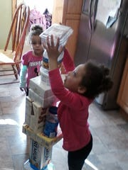 Cera and Merah stack up recyclables, a fun activity to keep the kids busy during Thanksgiving prep.