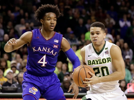 Kansas guard Devonte' Graham (4) defends as Baylor guard Manu Lecomte (20) of Belgium moves to the basket in the second half of an NCAA college basketball game Saturday, Feb. 10, 2018, in Waco, Texas. (AP Photo/Tony Gutierrez)