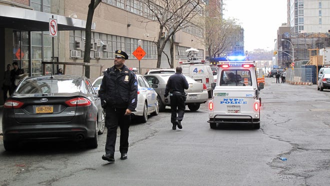 New York Police Department officers police walk in front of a high-rise apartment building where they said a 35-year-old man and a 3-year-old child died after plummeting from the building in New York on Dec. 22, 2013.