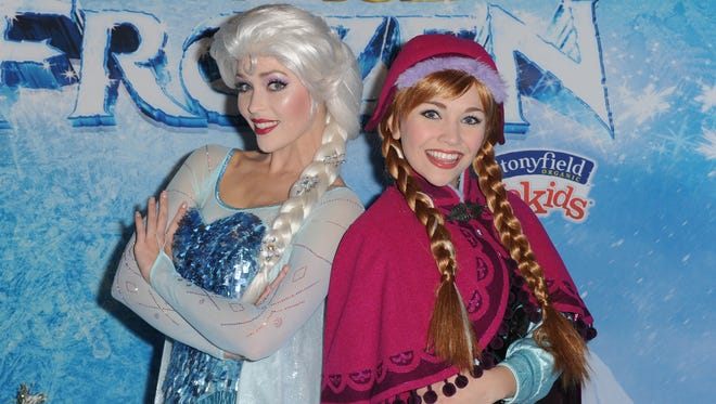 """Elsa the Snow Queen (left) and Princess Anna attend the """"Frozen"""" celebrity premiere presented by Disney On Ice and held at the Staples Center on Dec.10 in Los Angeles."""