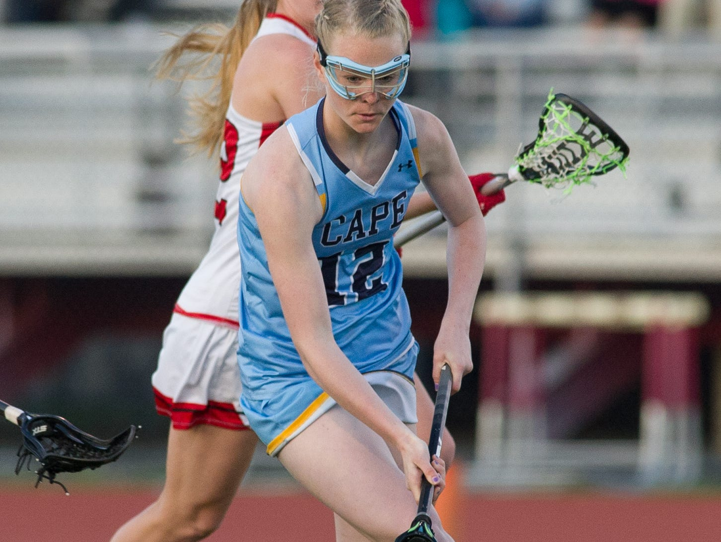 Cape Henlopen's Victoria Lockwood (12) scoops up a loose ball in their 12-10 win over Polytech.