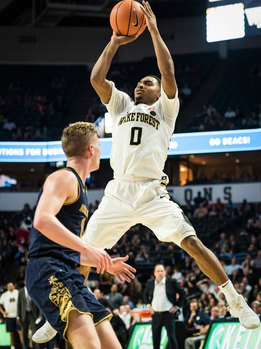 Wake Forest guard Brandon Childress (0) shoots over Notre Dame junior guard Rex Pflueger in the second half of an NCAA college basketball game Saturday, Feb. 24, 2018, in Winston-Salem, N.C. Notre Dame defeated Wake Forest, 76-71. (Allison Lee Isley/The Winston-Salem Journal via AP)