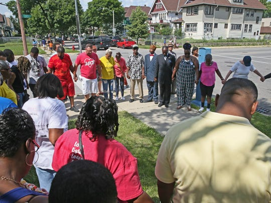 People join hands in prayer in a circle before they begin a walk through the neighborhood. A community cleanup and prayer walk were held at N. 39th St. and W. Center St. in Milwaukee on July 8, 2017, in honor of 16-year-old Emani Robinson who was shot and killed.