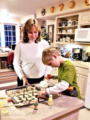 The Kellam family bakes 45 dozen cookies of nine varieties, placed in decorative cookie cans, to be eaten on Christmas Eve.