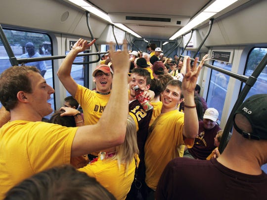 ASU fans ride the light rail to the game in Tempe in