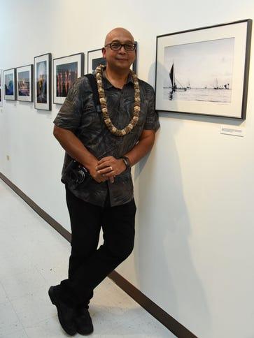 Photojournalist Manny Crisostomo poses next to his