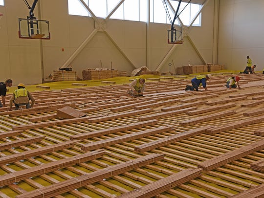 Construction crews install the wood floor to the new multi-purpose gymnasium at the new Foothills Activity Center  at Foothills Mall.  The gymnasium, located on the third floor, is connected to the new  parking garage.