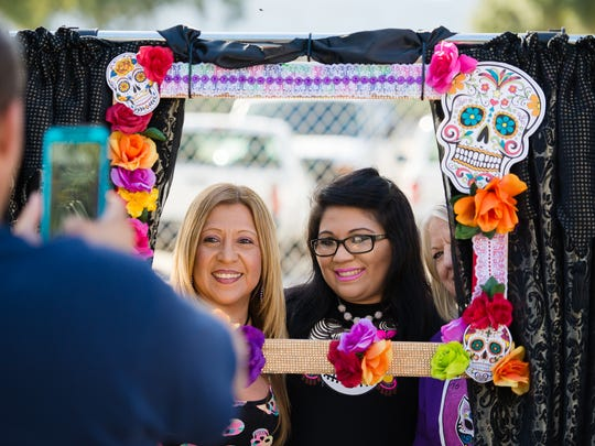 Robina Ramos and Esme Salazar take a photo at a vendor's booth Saturday, Oct. 29, 2016, during the Día de los Muertos Street Festival in downtown Corpus Christi.