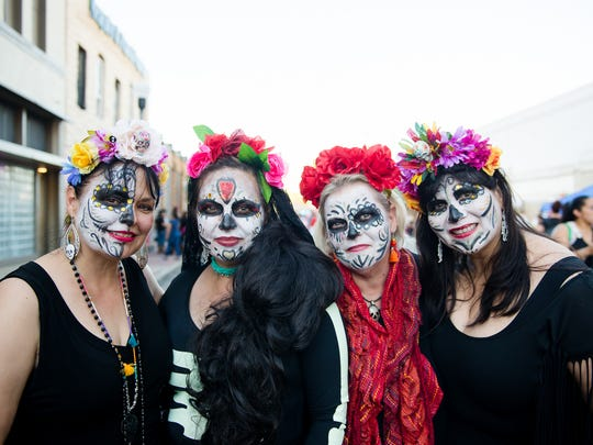 Nancy Cantu (from left), Roberta Morena, EJ Brown and Nancy Barnett wear calaveras face paint and flower wreaths Saturday, Oct. 29, 2016, during the Día de los Muertos Street Festival in downtown Corpus Christi.