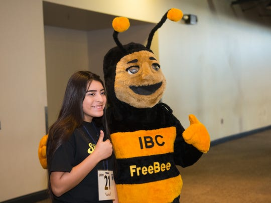 Jessica Rivera takes a photo with IBC Bank's bee mascot. The bank was a co-sponsor of the event.