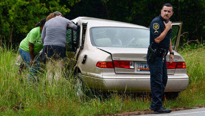 An Anderson police officer stands by a car involved in an accident at Gossett Street and Williamston Road in Anderson on Friday morning.
