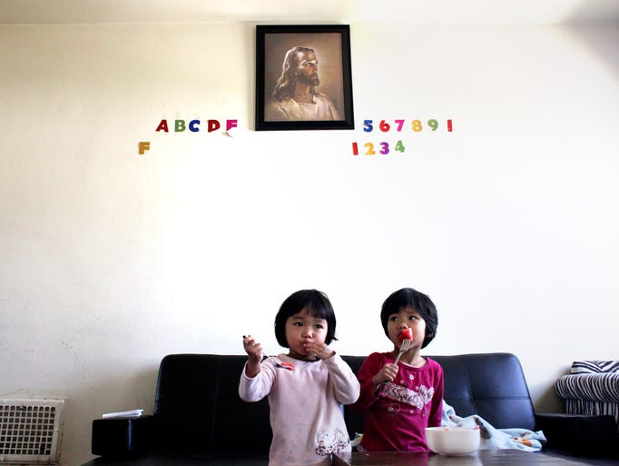 Joyce Mawi, left, and Blessy Mawi, right, eat watermelon while watching television at Kingston Park Apartments. April 17, 2014