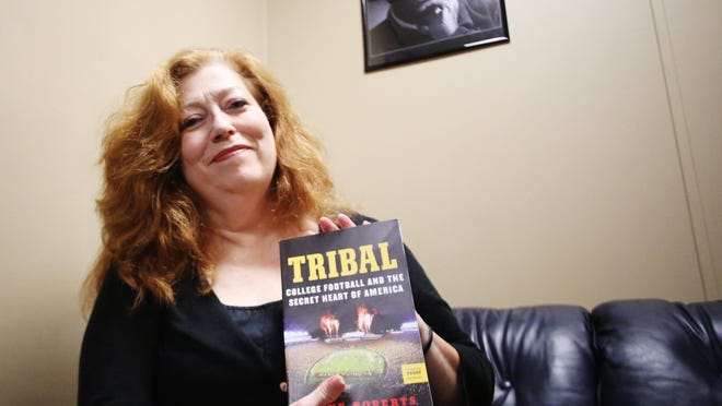 """Florida State University professor Diane """"D.K."""" Roberts is releasing her latest book, """"Tribal: College Football and the Secret Heart of America."""" Here, she holds a copy of her book in the Democrat's office under a photo of former FSU head football coach Bobby Bowden, whom she criticizes in the book."""