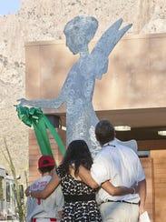 Dallas, Roxanna and John Green look at the sculpture