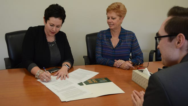 Palm Springs Unified School District Superintendent Sandy Lyon, left, signs an agreement with the University of La Verne to automatically accept district students.