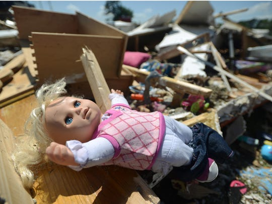A child's doll lies atop the twisted wreckage of a mobile home destroyed by the tornado that ripped through Highlands trailer park in Pearl on Monday.