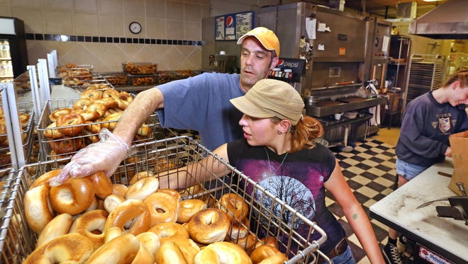 Bagel Fair workers (from left) Joseph Farber, Sharon Maddox and Elizabeth Pauker hustle to serve walk-in customers and fill more than 50 preorders on Wednesday morning, Sept. 23, 2015 at the shop in Nora Plaza, 1300 E. 86th St., Indianapolis. Yom Kippur is the busiest day of the year for the specialty baker. Baker Jon Hinkle began his shift at 4 a.m. to bake about 300 dozen bagels.
