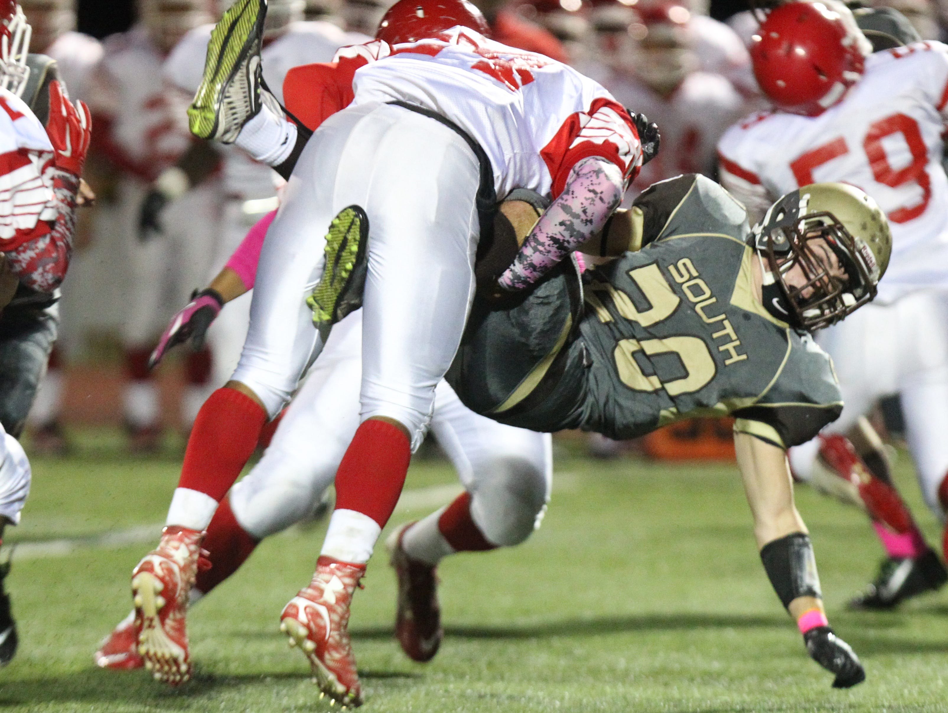 Clarkstown South's Sam Mistrella is tackled by North Rockland's Kenny Perry during their Class AA qualifying round game at Clarkstown South Oct. 16, 2015.