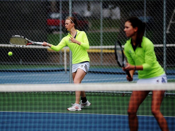 Augustana's Katie Jesperson, left, hits the ball as teammate Jessa Richards looks on during a doubles tennis match against Northeastern State's Martina Bruzikova and Valeriia Efimenko during the 2014 NCAA Division II Central Region No. 2 women's tennis championship on Sunday, May 4, 2014, at the Huether Tennis Centre in Sioux Falls. (Joe Ahlquist / Argus Leader)