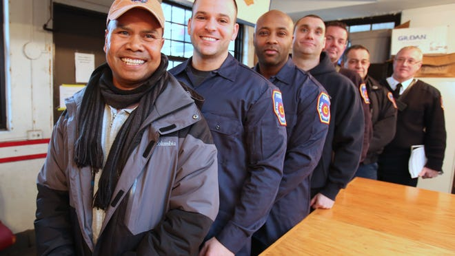 Firefighter Francis Hosei, left, at the White Plains Fire Department headquarters with the firefighters who saved his life after he had a heart attack on the job last November. They are, starting behind Hosei, firefighters Tonin Bucaj of White Plains, Percy Johnson of White Plains, Lt. Thomas Glass of Mahopac, firefighters Rocco Presto of Harrison and Sal Birittieri of White Plains, and Deputy Chief Richard Houlihan of Yonkers. Not present was Lt. Eric Bratberg, of Harrison.