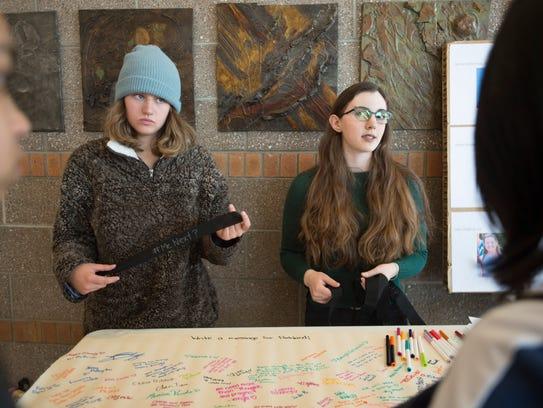 Asha Olick and Nina Shelanski hand out arm bands showing