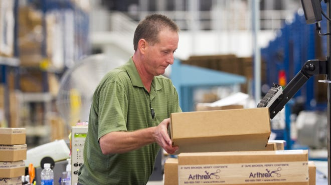 Kevin Roberts organizes boxes to be shipped at the warehouse, which has been in operation since 2012.
