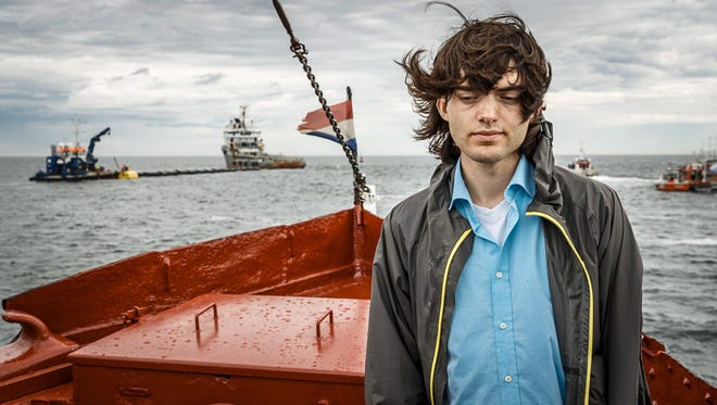Dutch inventor Boyan Slat stands on a boat in front of first prototype set up of 'The Ocean Cleanup', which is being installed off the Dutch coast near Scheveningen, The Netherlands, 23 June 2016.