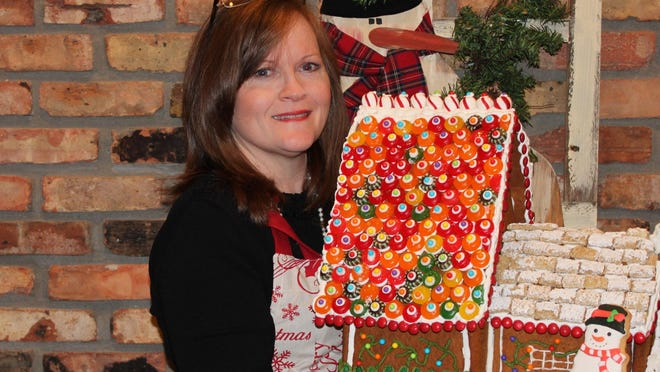 Kelly McDaniel poses with a gingerbread house creation at one of her recent holiday decorating parties. The Monroe mom has hosted them annually since 2000.