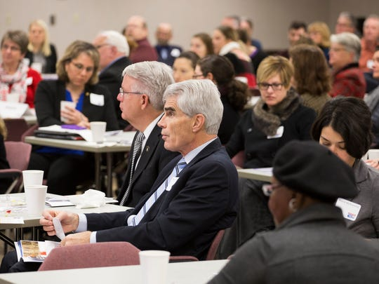 Legislators and community leaders listen Tuesday at