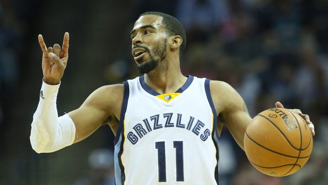 Memphis Grizzlies guard Mike Conley (11) signals to his team as he dribbles in the first quarter against the Phoenix Suns at FedExForum.