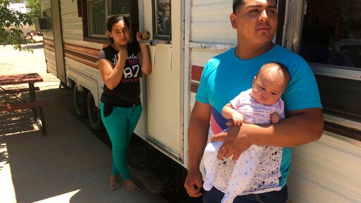 FILE - In this May 25, 2018, file photo, Jose Espinoza, 18, stands outside his trailer with his 4-month-old infant, Emmily, and wife, Maria Rodriguez, 19, in Vado, N.M. while speaking about making only $50 a day picking onions. New Mexico's child poverty rate rose slightly and continues to rank near the bottom nationally despite improvements in the state's economy, a child-advocacy group said Wednesday, Jan. 15, 2020. The 2019 New Mexico Kids Count Data Book, released by New Mexico Voices for Children, found 26% of the state's children in 2018 remained at or below the federal poverty line. That places the state back to 49th nationally in child poverty.