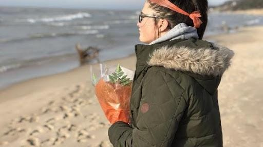 Lilly Goodrich stands at the Lake Michigan shoreline with flowers for her best friend, Eliza Trainer, 16, who is presumed dead after she was swept off the pier Jan. 1 at Holland State Park. Lilly's brother, Kade,  also was swept in but escaped and ran for help.